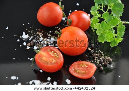 Fresh cherry tomato on black background - stock photo