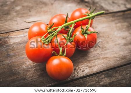 Fresh cherry tomato on rustic vintage wood - stock photo