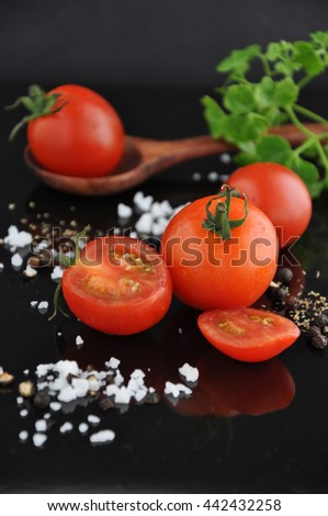 Fresh cherry tomato with salt and pepper on black background - stock photo
