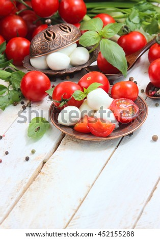 fresh cherry tomatoes and mozzarella on a white wooden background