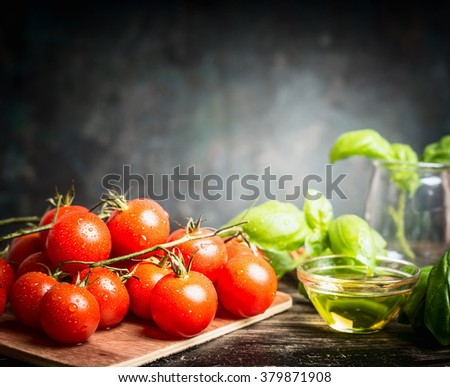 Fresh cherry tomatoes bunch with basil and oil on dark rustic background, side view, place for text. Italian food ingredients. - stock photo