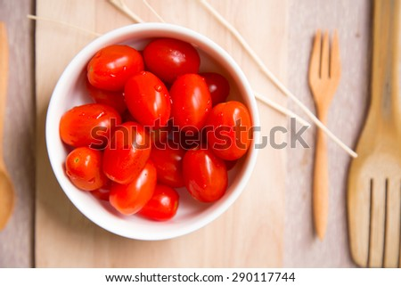 Fresh cherry tomatoes in white bowl decorated with wooden kitchen tools.
