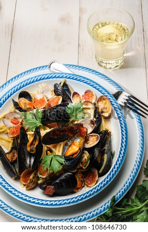 Fresh cherry tomatoes, mussels and clams parsley. Typical Italian Dish - stock photo