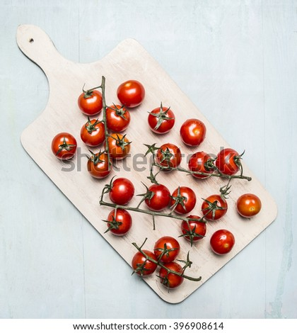 Fresh cherry tomatoes on a branch on a white cutting board on wooden rustic background top view - stock photo