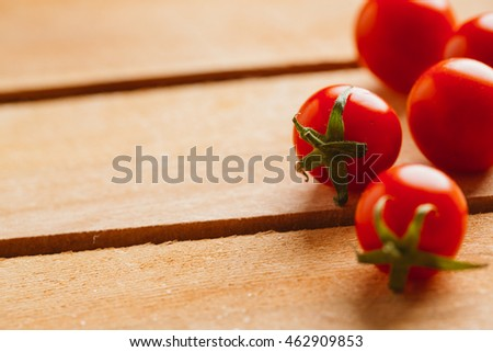 Fresh cherry tomatoes on a wooden background.