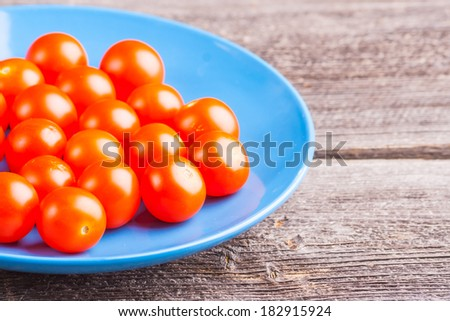 fresh cherry tomatoes on blue plate