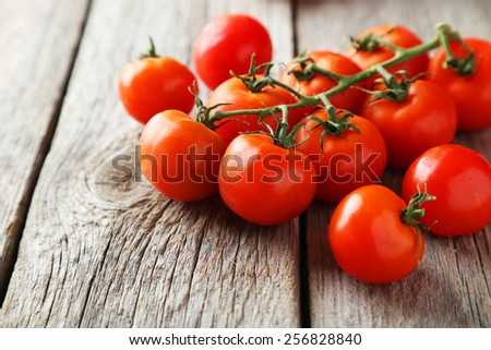 Fresh cherry tomatoes on grey wooden background - stock photo