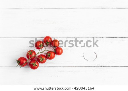 Fresh cherry tomatoes on wooden white background. Cherry tomatoes on a branch. Flat lay, top view  - stock photo
