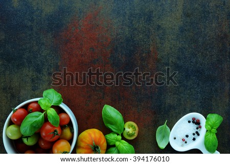 Fresh cherry tomatoes with basil and coarse salt for use as cooking ingredients with a halved tomato with copyspace - stock photo