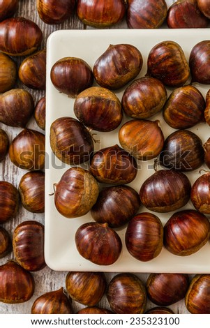 Fresh chestnuts in a white plate on wooden white background