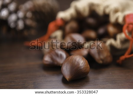 fresh chestnuts in sack bag on wooden table