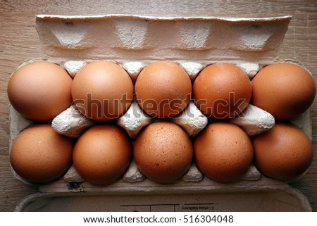 Fresh chicken eggs in cardboard box, top view