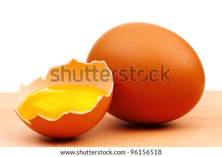 Fresh chicken eggs on wooden board over white background