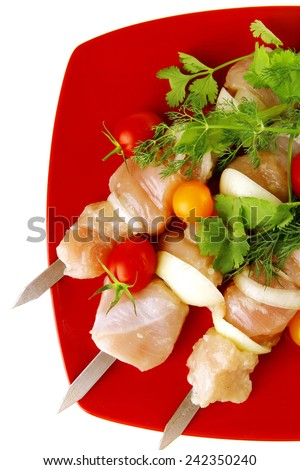 fresh chicken kebabs on red served with cherry - stock photo