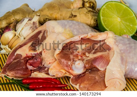 fresh chicken legs with ingredients on bamboo wrap - stock photo