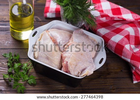 Fresh chicken meat in bowl  on  dark painted wooden planks. Selective focus. Rustic style. - stock photo