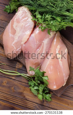 Fresh chicken meat with herb parsley and dill on wooden board on table . Selective focus. Rustic style. - stock photo