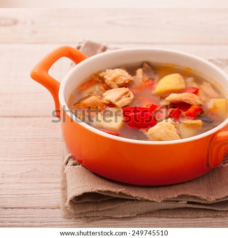 Fresh chicken soup with vegetables on white wooden table. Cutlery on a linen tablecloth. rustic style