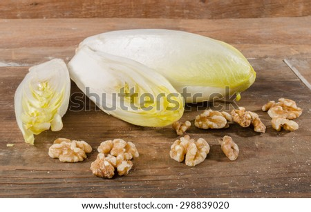 Fresh chicories with walnuts on wooden background