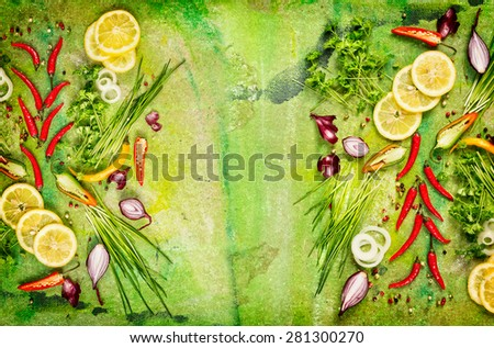 Fresh chili,onion,lemon and aromatic herbs various for cooking on green rustic background, top view, frame - stock photo