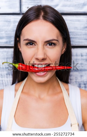Fresh chili pepper. Cropped image of beautiful young smiling woman in apron holding red chili peppers while standing in front of wooden background - stock photo