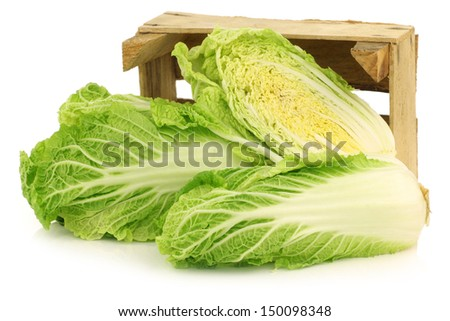 fresh chinese cabbage and a cut one in a wooden crate on a white background - stock photo