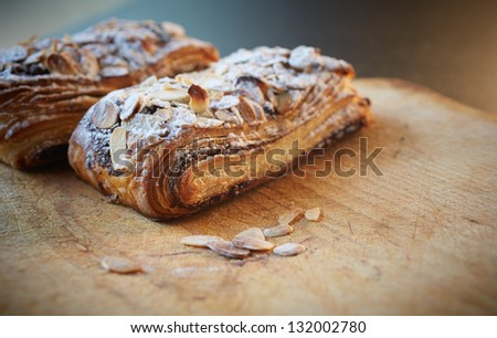 Fresh chocolate and Almond rollover croissant pastry, sprinkled with icing sugar on a brown wooden serving board with copy space  - Shallow Depth of Field (DOF) - stock photo