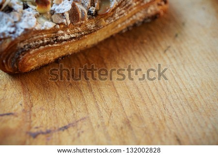 Fresh chocolate and Almond rollover croissant pastry, sprinkled with icing sugar on a brown wooden serving board with copy space  - Shallow Depth of Field (DOF)