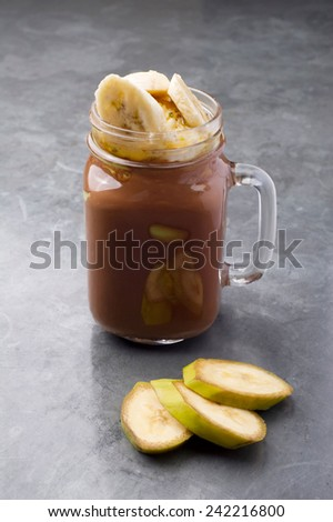 Fresh chocolate and banana smoothie on a gray vintage table - stock photo