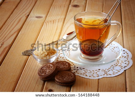 fresh chocolate cookies and hot black tea over wooden table
