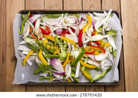 Fresh chopped onions and peppers on a baking sheet - stock photo