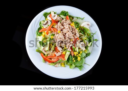 fresh chopped tuna salad with spinach on  black background