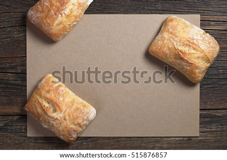 Fresh ciabatta bread on dark wooden table with empty paper, top view. Space for your text