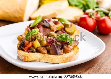 fresh ciabatta bread with a tasty homemade caponata.  - stock photo