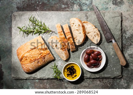 Fresh ciabatta with olive oil and olives on stone slate background - stock photo