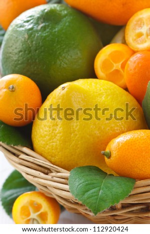 Fresh citrus fruit with leaves in a wicker basket. - stock photo