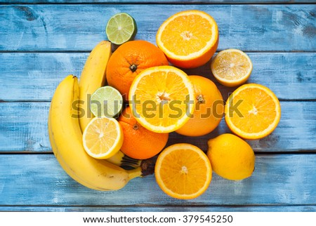 Fresh citrus fruits - lime, lemon, orange, grapefruit and banana at wooden table. Top view. - stock photo