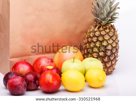 Fresh citrus fruits of pineapple orange juicy grapefruit yellow lemon ripe nectarine purple plum red pomegranate and green apple near brown paper pack on white background copyspace, horizontal picture - stock photo