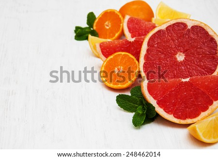 Fresh citrus fruits with green mint on a old white wooden background - stock photo