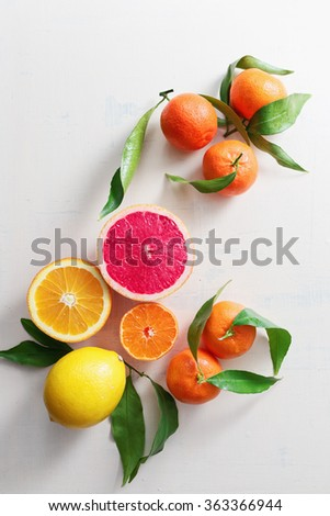 Fresh citrus fruits with leaves on table - stock photo