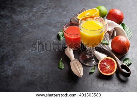 Fresh citruses and juice on dark stone background. Oranges and limes. View with copy space - stock photo