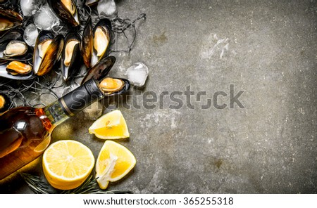 Fresh clams on the fishing net with the lemon and wine. On the stone table. Free space for text . Top view - stock photo