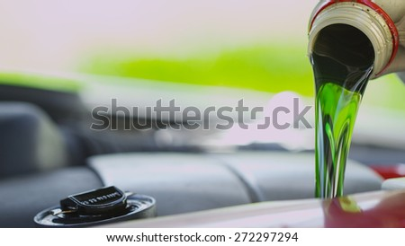 Fresh clean green oil being poured into a car engine - stock photo