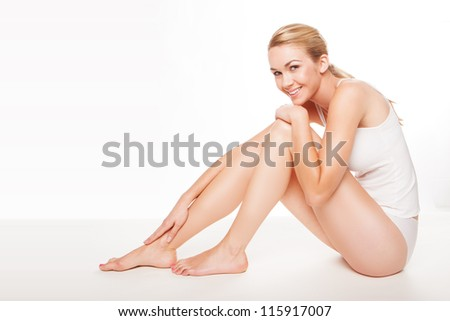 Fresh clean portrait of a long legged beautiful woman in lingerie with a lovely smile sitting on the floor