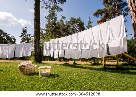 fresh clean white towels drying on washing line in outdoor - stock photo