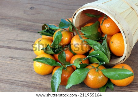 fresh clementine fall out of bucket on rustic table  - stock photo