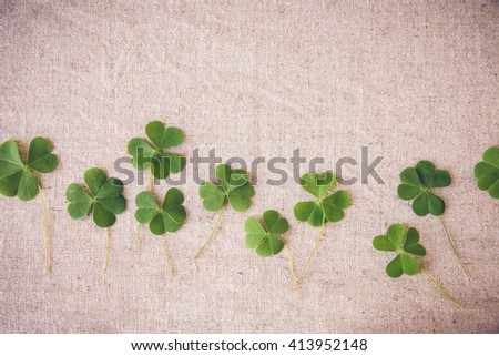 Fresh clovers leaves on linen, St Patricks day copy space background - stock photo