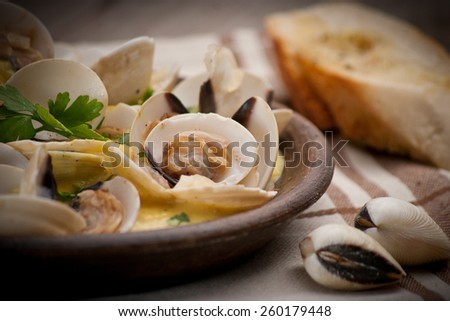 Fresh Cockle clams (Venus, Meretrix) with wine sauce. Portuguese dish. - stock photo