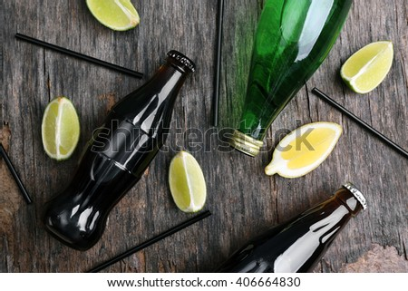 Fresh cocktail preparation: slices of citruses, straws and bottles on rustic table background, top view - stock photo