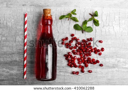 Fresh cocktail preparation: soda bottle, pomegranate, straw  on grey table background, top view - stock photo